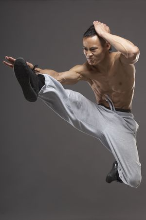 arts: Young asian martial arts man over gray background