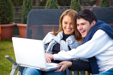 Happy Young couple surfing the internet outside photo