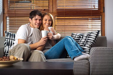 pareja en casa: Feliz pareja de j�venes se divierten en el sof� Foto de archivo