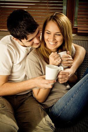 hombre tomando cafe: Feliz pareja de jóvenes se divierten en el sofá Foto de archivo