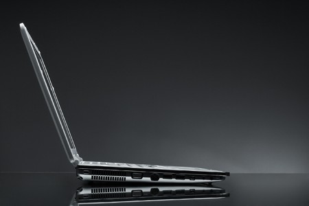 Laptop shot on reflective table on grey background, view from the side Stock Photo - 4192655