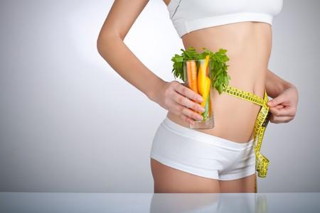 cintura: Concepto imagen de una mujer con un vaso de verdura en frente de su cuerpo