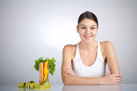 Woman looking at the camera near a glass filled with veggies Banque d'images
