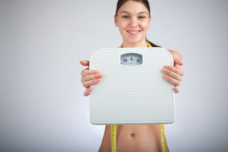Woman with bathroom scale and measuring tape, focus on bathroom scale Stock Photo - 4373714