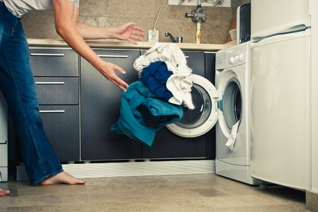 laundry concept: Concept Man throwing his laundry into the washing machine
