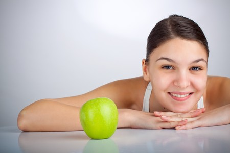 Happy woman smiling near a green apple Stock Photo - 4544640