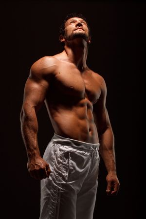 sexy muscular man: Dramatic image of a beautifully sculpted bodybuilder
