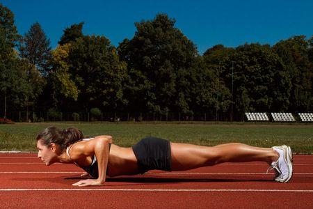 energy work: Athletic woman working out on track Stock Photo