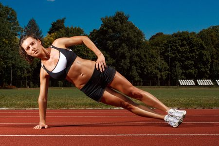 push up: Athletic woman working out on track Stock Photo