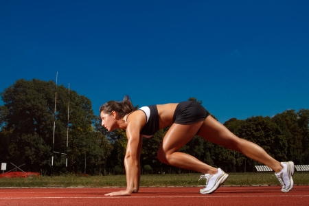 jogging track: Athletic woman on track starting to run