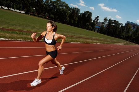 Athletic woman running on track  Stock Photo