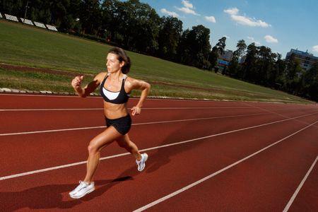 Athletic mujer corriendo en la pista