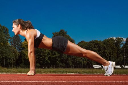 stretched out: Athletic woman working out on track Stock Photo