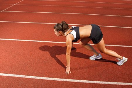 Athletic woman on track starting to run photo