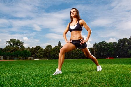 outdoor training: Athletic woman working out on field Stock Photo