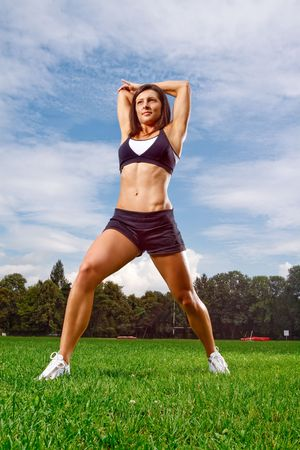 Athletic woman working out on field photo