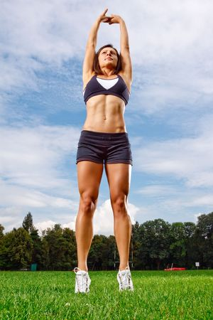 stretched out: Athletic woman working out on field Stock Photo