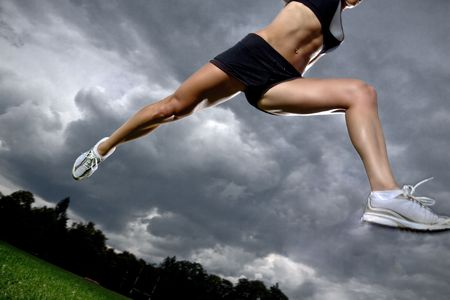 woman running: Athletic woman running before the storm Stock Photo