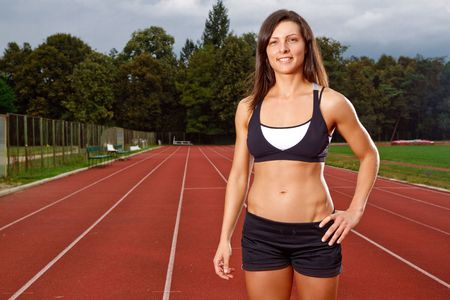 Athletic woman with a big smile on track photo