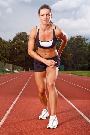 Athletic woman in start position on track photo