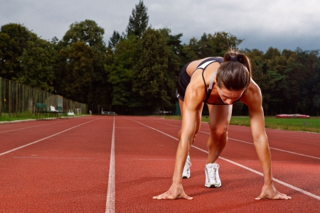 running track: Athletic woman in start position on track