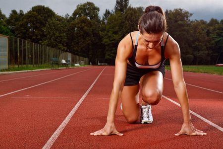 start of race: Athletic de la mujer en posici�n de inicio en la pista