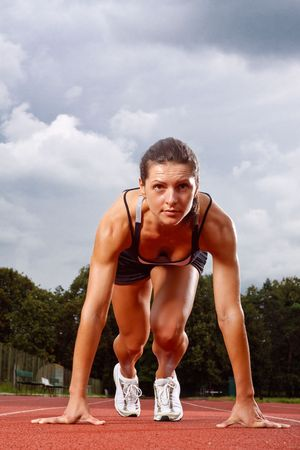 Athletic woman in start position on track  Stock Photo
