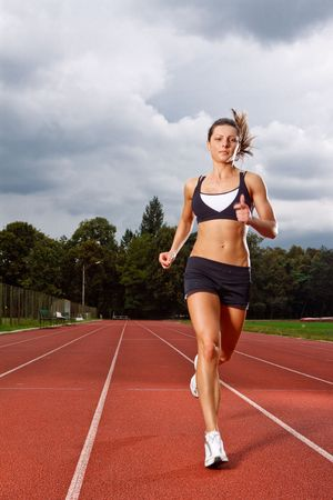 athletic girl: Athletic woman running on track  Stock Photo