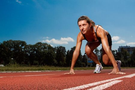 Athletic woman on track starting to run Stock Photo - 5443091