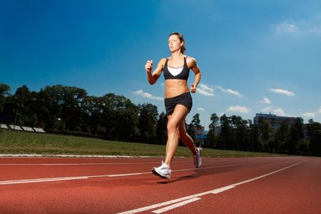 running track: Athletic woman running on track  Stock Photo