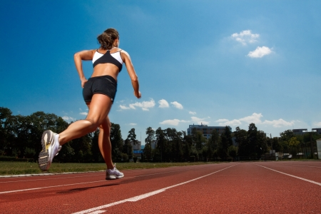 running on track: Athletic woman running on track  Stock Photo