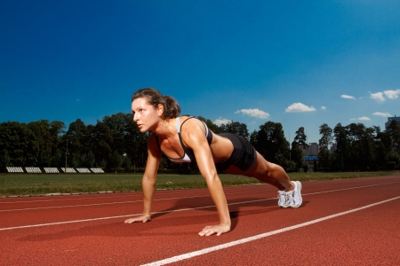 pushup: Athletic woman working out on track Stock Photo