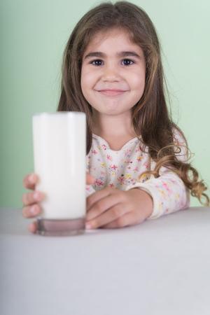 Little hispanic girl  holding a glass of milk