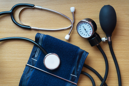 Stethoscope and sphygmomanometer over a wooden table