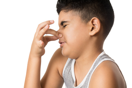 Hispanic child blocks his nose with one hand isolated on white Stock Photo