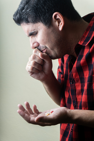 Hispanic man coughing with a bunch of pills on the left hand