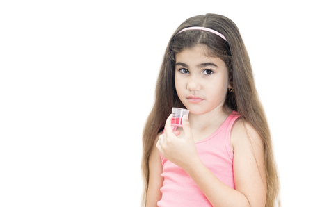 Little Hispanic girl looks upset while she tries to drink his medicine isolated on white Reklamní fotografie