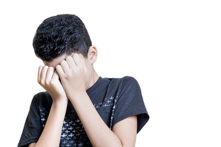 Frightened hispanic kid cover his face with both hands isolated on white