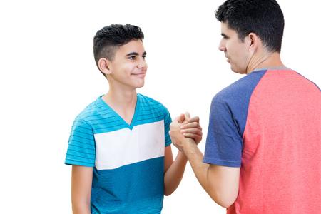 Père latin et son fils adolescent se serrant la main isolés sur blanc
