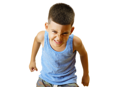 Little hispanic kid in an aggressive posture isolated on white.