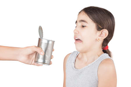 Little girl make a disgusted grimace to an spoiled canned food