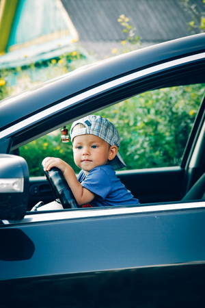 Little boy driving a car looking out the window Stock Photo