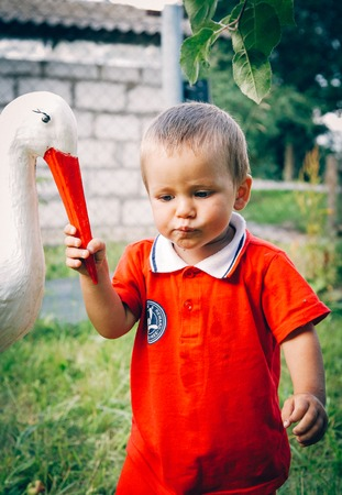 The child took the beak of a stork and holds onto it Imagens