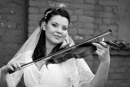 Beautiful bride in white dress playing violin melody,black white Reklamní fotografie - 102137593