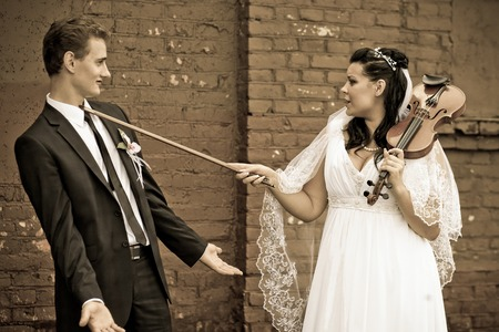 The bride is having fun with the groom playing with the violin, vintage Banco de Imagens