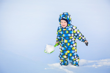 A child in winter with a green shovel sneaks through the snow-covered field