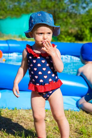 On a hot day the girl stood in swimsuit in hearts near the inflatable blue pool Standard-Bild