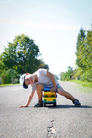 Preschool boy playing on the asphalt road with a large toy car