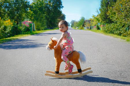 Baby swinging alone on a toy wooden horse outdoors