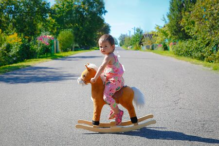 Little girl alone the road playing with a toy horse